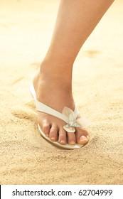 Woman foot on beach