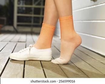 woman foot in orange socks  on wood deck.