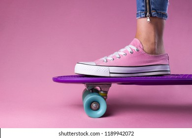 Woman foot pink sneakers on penny board pink background