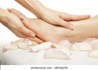 woman foot receiving gentle massage on bed with rose petals, isolated with work path