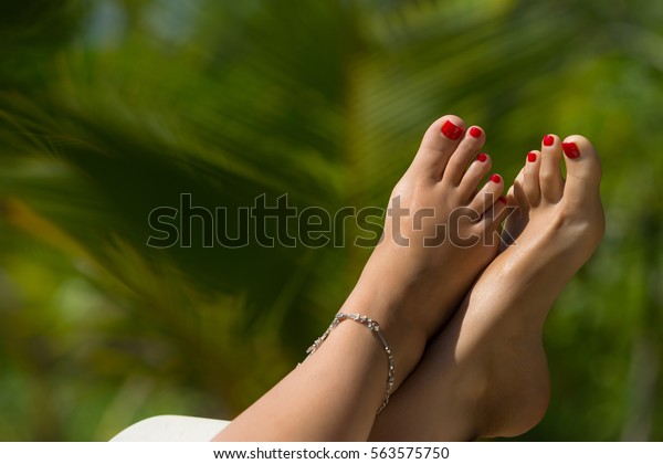 Woman foot with red pedicure in the tropical beach conceptual image of vacation