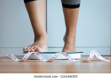 Woman foot stepping on weigh scales with tape measure in foreground,Weight loss,Body and good health concept