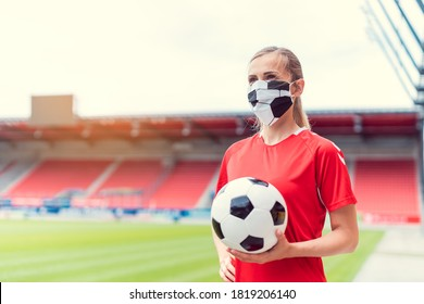 Woman football player wearing face mask in empty stadium waiting for the season to open