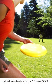 woman in the foreground about to throw a disc to a man squatting in the background, grass and line of trees visible in the background