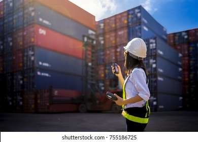 Woman Foreman control loading Containers box from Cargo freight ship for import export.