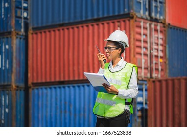 Woman Foreman in hardhat and safety vest holding holding clipboard checklist and talks on two-way radio control loading containers box from cargo