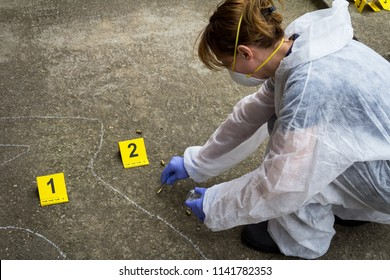 Woman forensic expert collects evidence at the crime scene. He packets the bullet shell in the bag