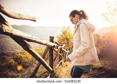 Woman at a forest trail covered in ladybugs during sunset