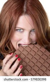 woman forgetting about the diet and eating a large chocolate bar