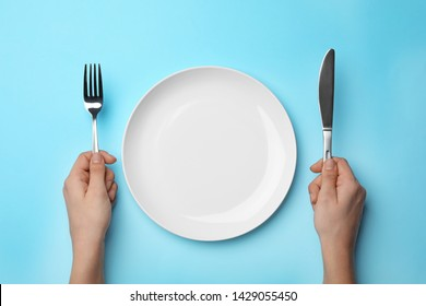 Woman with fork, knife and empty plate on color background, top view
