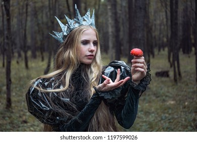 A woman in the form of an evil witch holding a poisonous mushroom in a dense forest.