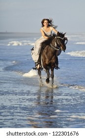 woman in formal dress riding galloping horse through surf