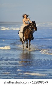 woman in formal dress riding horse in the ocean