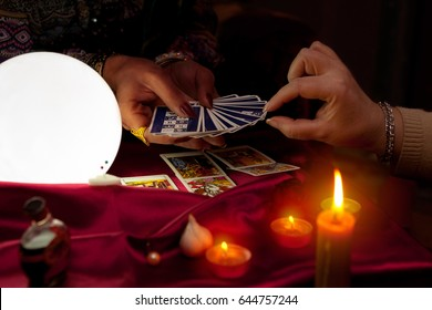 Woman fortune teller holding tarot cards in her hands and another woman picking the card