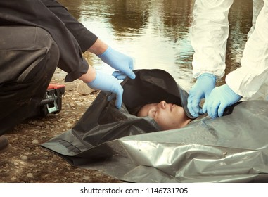 Woman found drowned on river bank in city placed in body bag for transportration