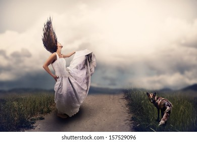 a woman and a fox on a path