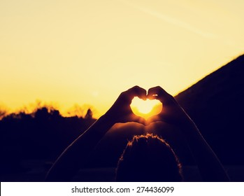 woman framing the sunrise or sunset while holding heart hands with retro instagram filter (shallow depth of field)