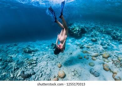 Woman free diver in bikini swim to deep in the tropical blue ocean