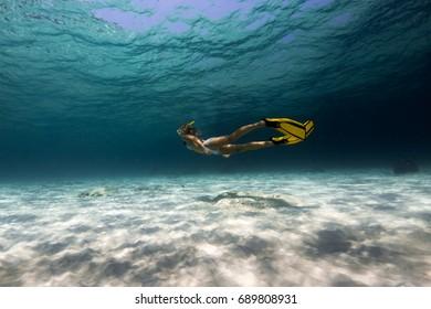 Woman freediver explores tropical underwater world, glides over sandy bottom