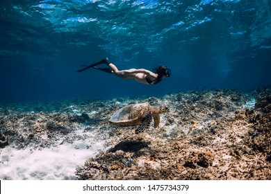 Woman freediver with fins glides underwater near sea turtle.