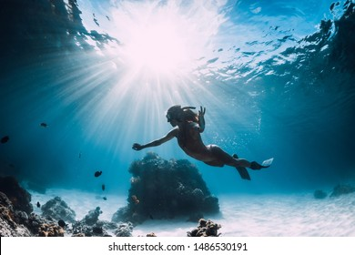 Woman freediver with fins swim over sandy sea with fish and sun rays underwater