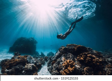 Woman freediver with fins underwater. Freediving and beautiful light in blue ocean