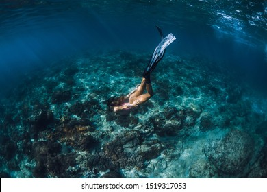Woman freediver with fins underwater. Freediving in blue ocean