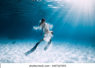 Woman freediver with fins and white sand over sandy sea. Freediving underwater in blue ocean