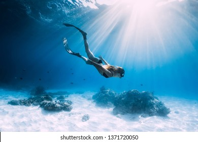 Woman freediver glides with fins. over sandy sea. Freediving and beautiful light in blue ocean