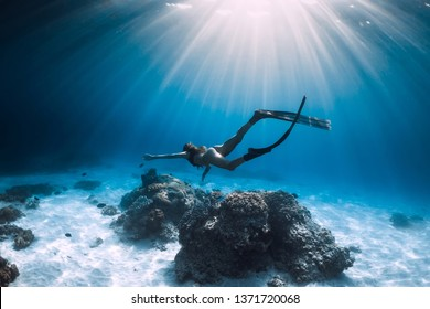 Woman freediver glides with fins over sandy sea. Freediving in blue ocean