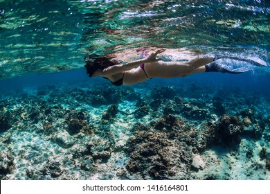 Woman freediver glides with fins over coral reef.