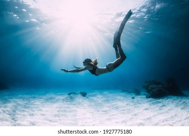 Woman freediver glides with fins. over sandy sea. Freediving and beautiful sunlight in blue ocean