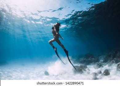 Woman freediver glides over sandy sea with fins. Freediving in ocean