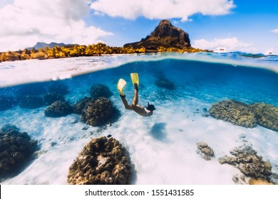 Woman freediver glides over sandy sea with yellow fins in transparent ocean. Freediving in Mauritius