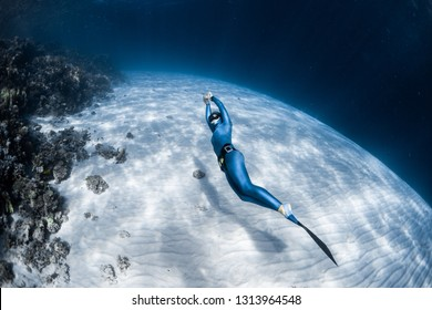 Woman freediver in monofin glides in the depth over the sandy bottom and looks at the surface
