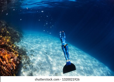 Woman freediver in monofin glides in the sea over the sandy bottom with school of fish and passes colorful coral reef