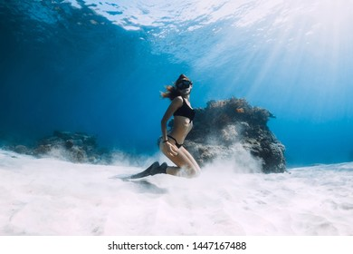 Woman freediver posing over sandy sea with fins. Freediving in Hawaii