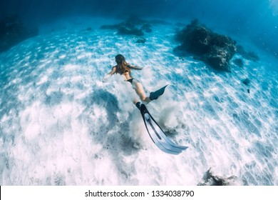 Woman freediver with sand over sandy sea with fins. Freediving underwater in Hawaii