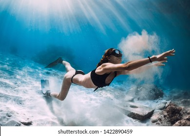Woman freediver with sand over sandy sea with fins. Freediving in Hawaii