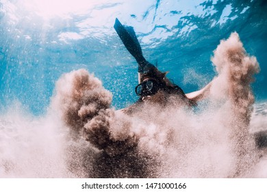 Woman freediver with sand over sandy sea with fins. Freediving underwater