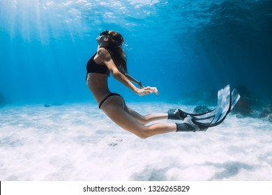 Woman freediver swim over sandy sea with fins. Freediving underwater in blue ocean