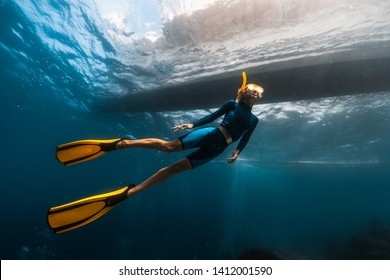 Woman freediver swims underwater under the boat
