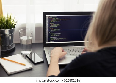 woman freelance programmer working from home. php website code on screen. Visible translations for page titles - Production, Project management, Partners and Contacts in Latvian and Russian languages