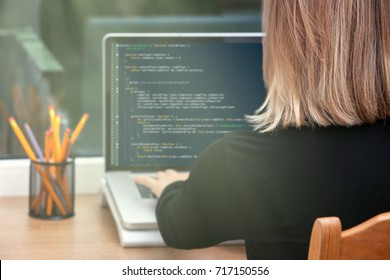 woman freelance programmer working from home. website code on screen