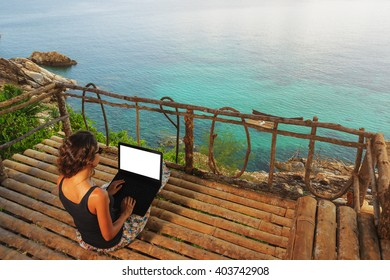 Woman freelancer sitting with laptop in bamboo alcove on a high. Amazing sea-view with blue lagoon.