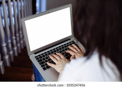 Woman freelancer using and working with laptop computer. Online business and self-employed concept. Female hands typing on a laptop computer with blank white screen ready for content.