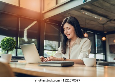 the woman freelancer is working her job on workplace at the coffee shop where she can work independently with the atmosphere warm.