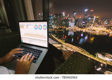 Woman freelancer is working using laptop computer in home office at night. Aerial city skyline view from window. Freelance lifestyle