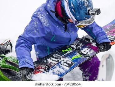 Woman freerider installs splitboard, in snow wild mountains.