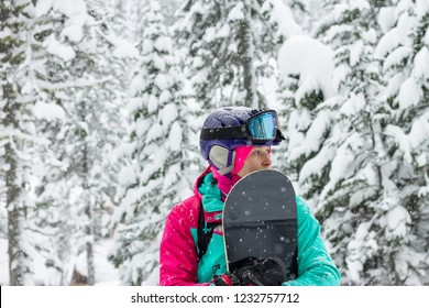 Woman freerider snowboarder standing in a snowy forest